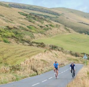 Two cyclists cycling up a hill on the Isle of Wight