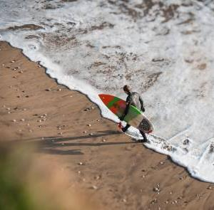 Surfer carrying surfboard on Isle of Wight Beach