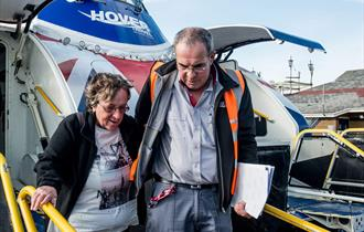 A man and woman disembarking from the Hovertravel craft.