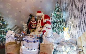 Father Christmas sitting with boy surrounded by presents and Christmas trees, The Needles, Isle of Wight, What's On