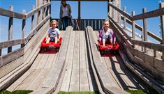 Children on the sledge slide at Tapnell Farm Park, Things to Do, Isle of Wight