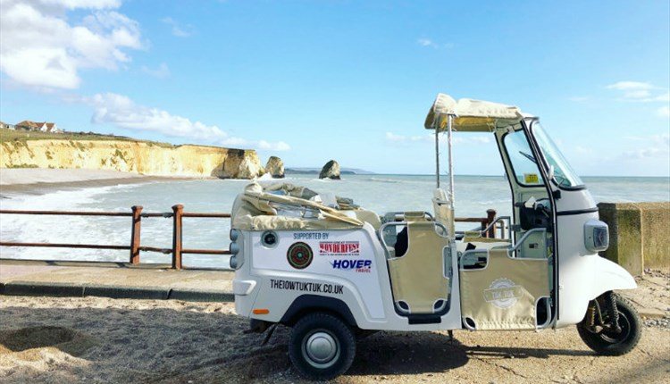 Isle of Wight Tuk Tuk Company, Tuk Tuk with top down stationary next to Freshwater Bay with cliffs in the back ground
