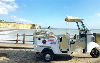 Isle of Wight Tuk Tuk Company, tuk tuk with top down next to Freshwater Bay with cliffs in background