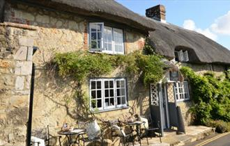 Outside of thatched cottage with outside eating area, Isle of Wight, Self-catering
